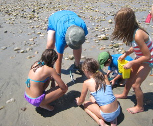 Four kids and one adult volunteer digging in sand