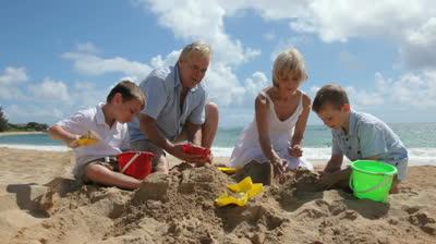 grandparents-play-with-grandchildren-at-beach